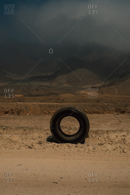 Tire on dirt road under stormy sky
