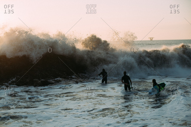 August 1, 2016: Surfers trying to paddle out while a big wave comes