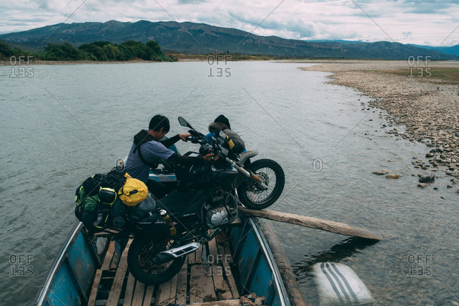 August 11, 2016: Man unloading motorbike from boat at edge of river