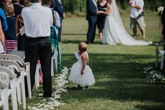 Cute toddler flower girl standing in aisle during wedding ceremony