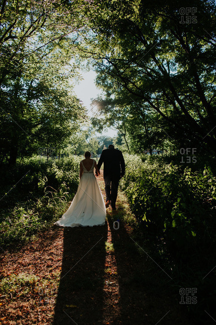 Back view of bride and groom walking on path in woods