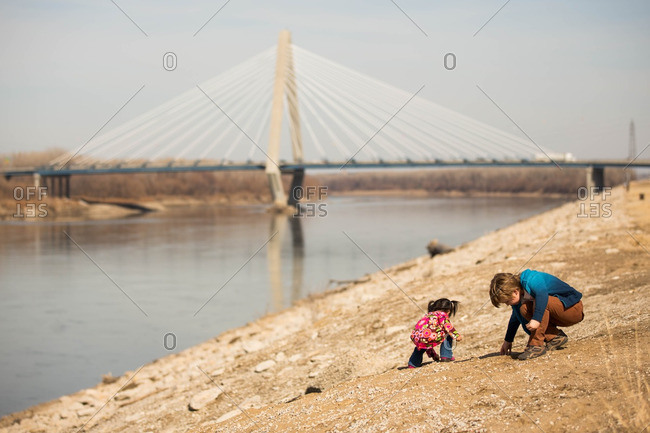 Two young children on riverbank picking up rock