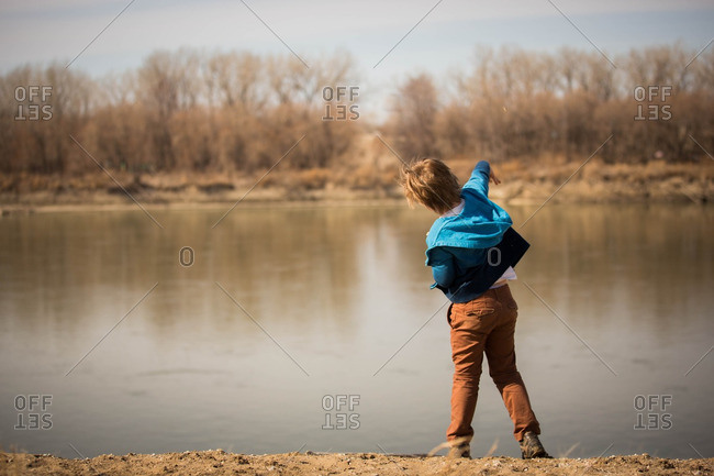 Young boy throwing rocks in river
