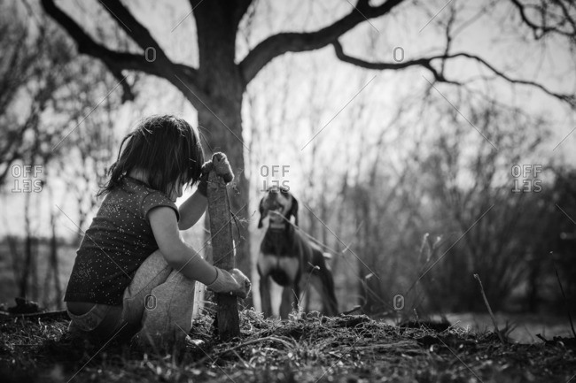 Toddler girl playing with stick while dog watches