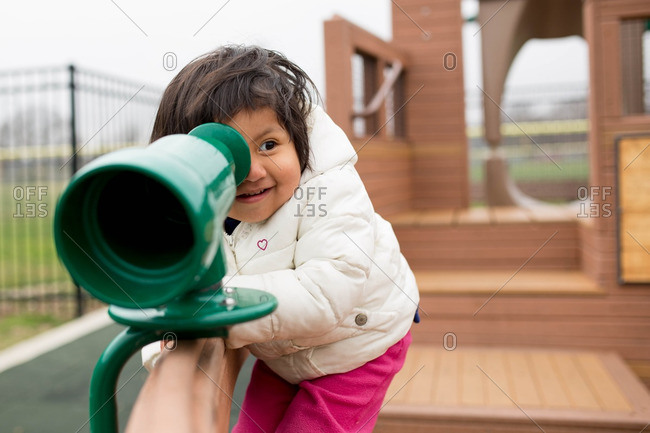 Toddler girl looking through telescope