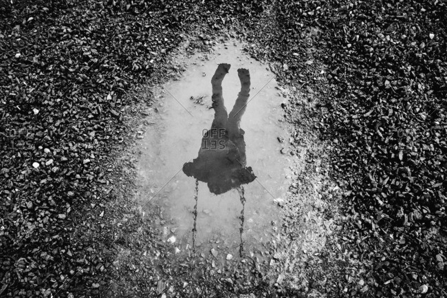 Puddle with reflection of child on swing