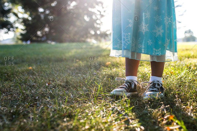 Child in sneakers and dress standing in grass