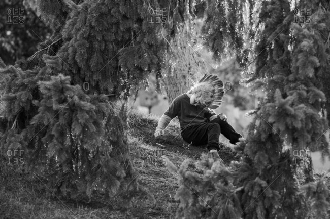 Young boy in Mohawk wig sitting on grass beneath tree branches