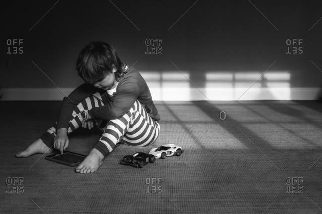 Boy in pajamas playing on tablet computer on rug
