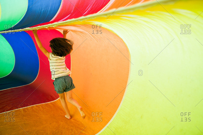 Young girl playing inside a rainbow parachute