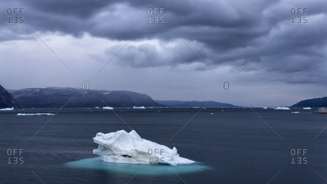 Dark clouds above an iceberg in the sea in Disko Bay, Greenland
