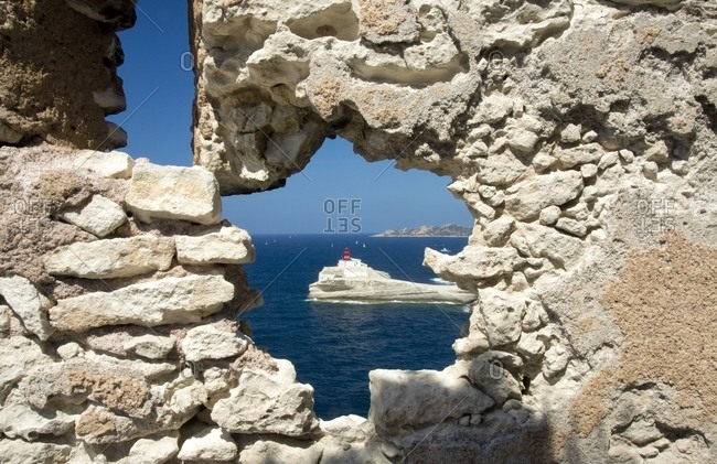 The lighthouse of Madonnetta seen through a natural opening in the ancient walls of Bonifacio, Corsica, France