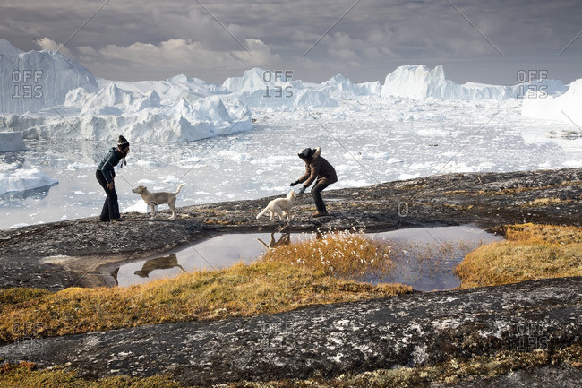 Disko Bay, Greenland - August 26, 2013: Women and two Greenland Husky pups in the background icebergs