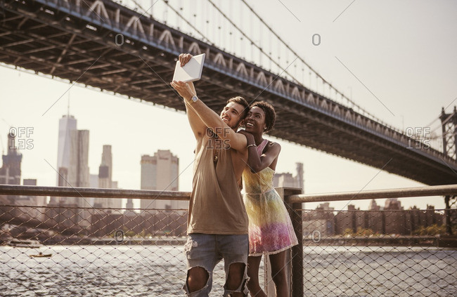 Multi-ethnic couple taking selfie through tablet computer against Manhattan Bridge and city skyline