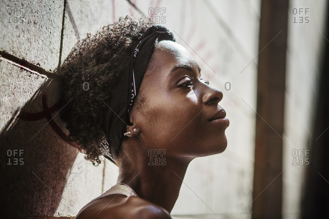 Close-up of thoughtful woman leaning on wall during sunny day