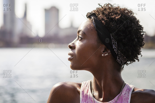 Portrait of thoughtful woman against river in city
