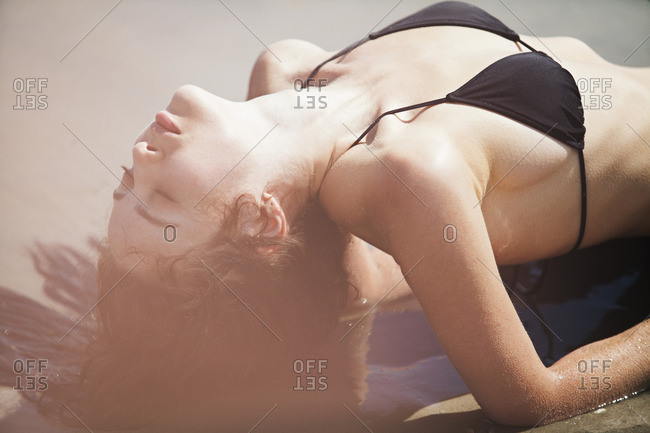 Close-up of seductive woman with eyes closed lying on shore at beach