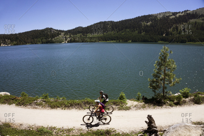 High angle view of cyclists riding bicycles on dirt road by lake