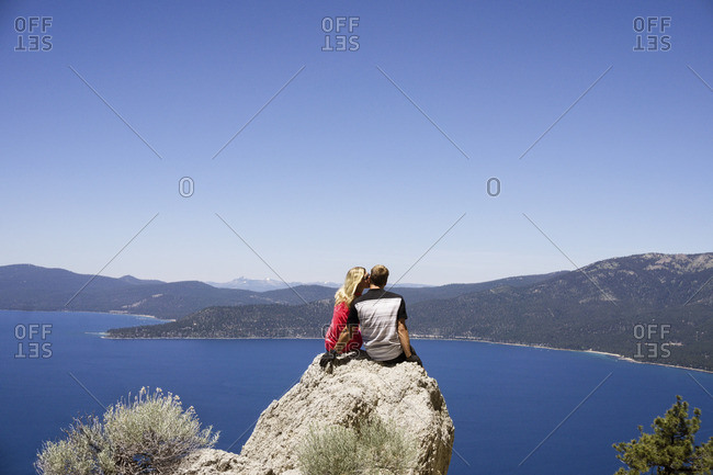 Rear view of couple sitting on cliff overlooking lake against clear blue sky