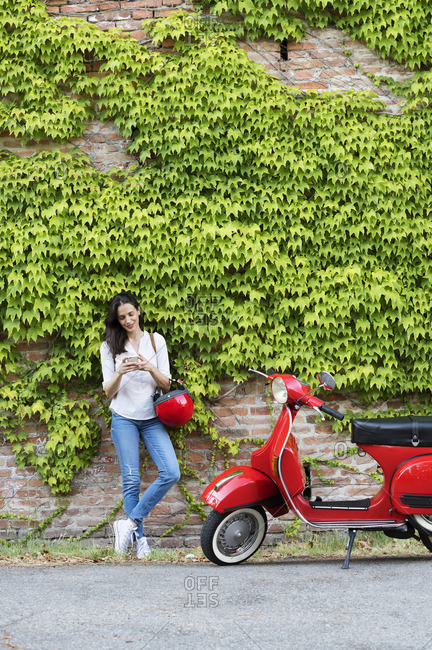 Woman using mobile phone while standing by motor scooter against ivy wall