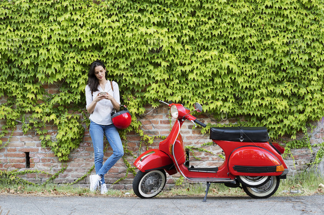 Woman using smart phone while standing by motor scooter against ivy wall