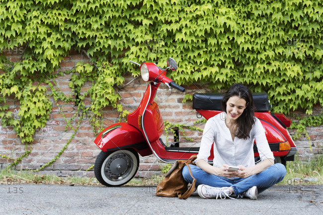Woman using mobile phone while sitting against motor scooter and ivy wall