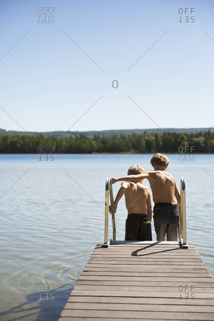 Rear view of boys moving down ladder on pier by lake against clear blue sky