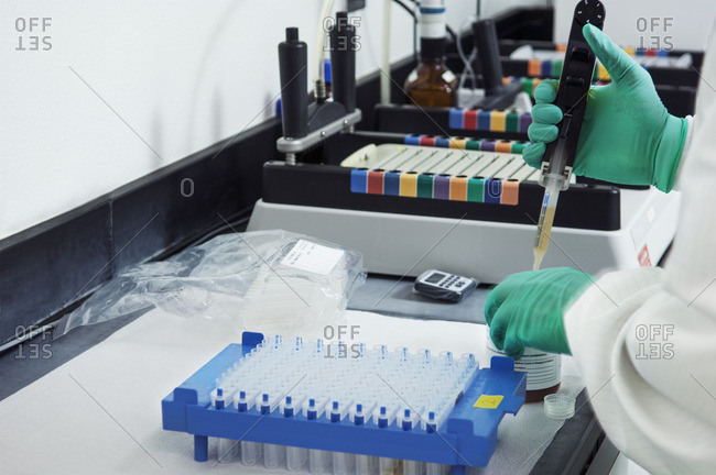 Cropped image of scientist pipetting sample into container in laboratory