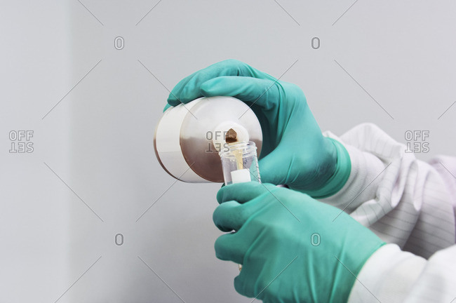 Cropped image of scientist pouring liquid in test tube at laboratory