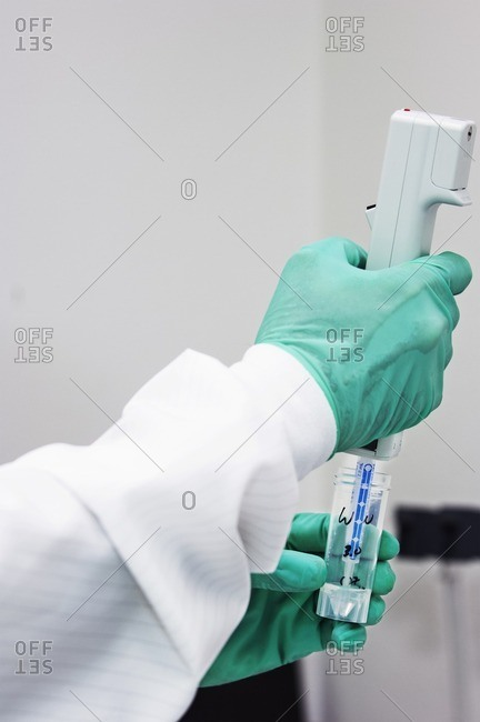 Cropped image of scientist pipetting sample into test tube in laboratory