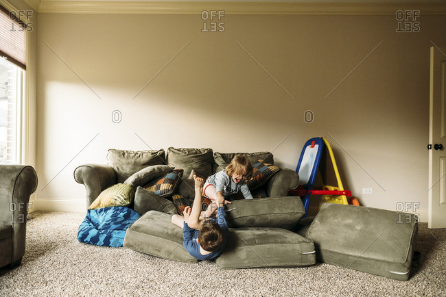 Boys playing with cushions at home