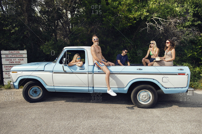 July 12, 2016: Cheerful friends enjoying while sitting in pick-up truck, Austin, Texas