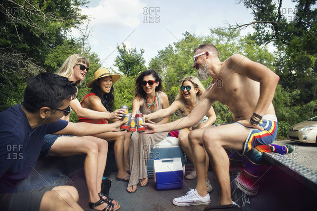 Friends toasting drinks while sitting in pick-up truck