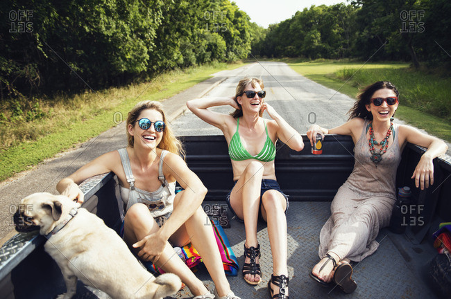 Female friends traveling in pick-up truck with pug