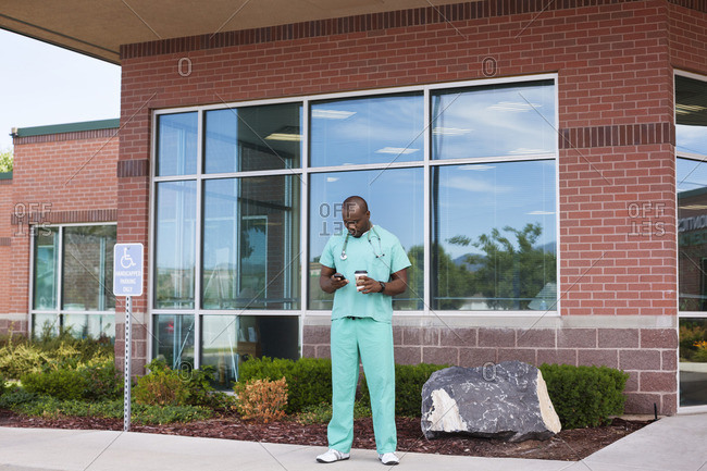 Doctor using phone while standing outside hospital
