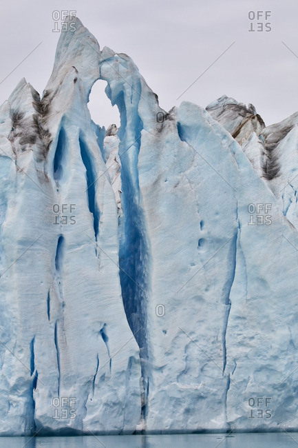 Blue ice cliff at the edge of the Knud Rasmussen Glacier with cracks and dirt