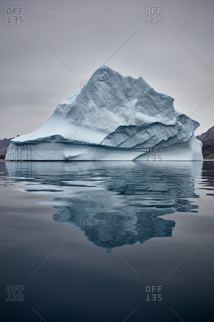 Iceberg floating and reflected in the sea near Greenland