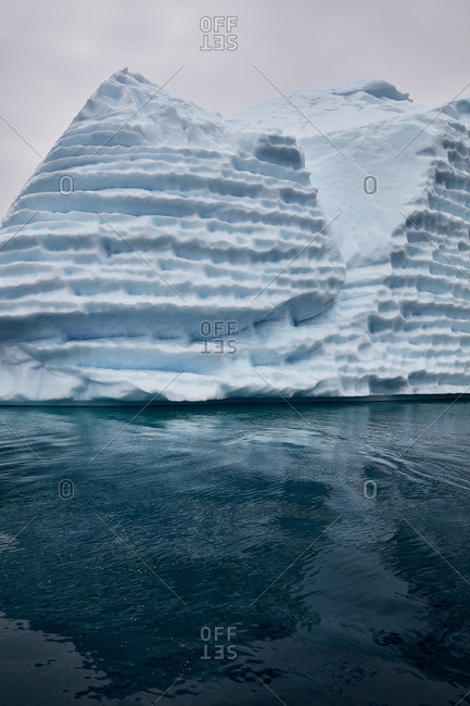 Ice formation with deep ridges reflected in water near the coast of Greenland