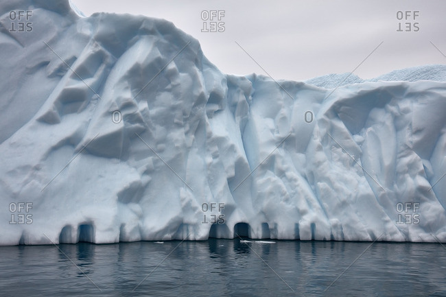 Wall of ice with holes carved by the sea near the coast of Greenland