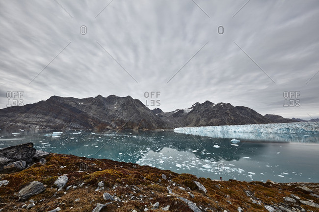 Cloud striations over a mossy shore at the Knud Rasmussen Glacier in Greenland