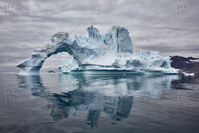Massive iceberg with an arch floating in a fjord, Greenland