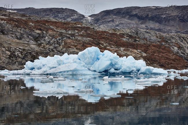 Large pieces of blue ice on a rocky shore in Greenland