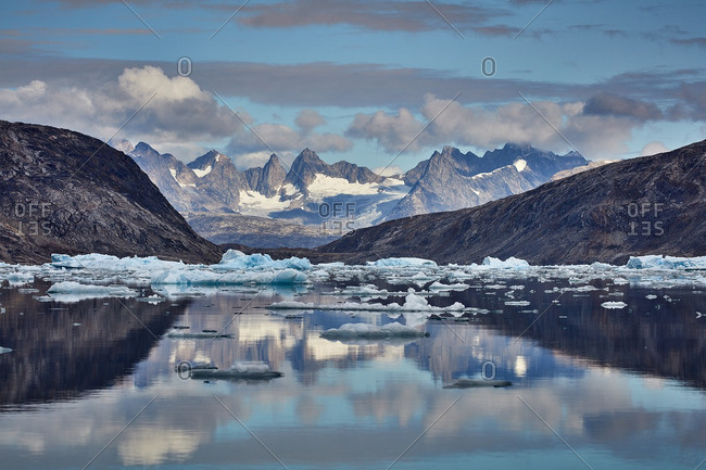 Reflections of ice and distant mountains in the Johan Petersen Fjord, Greenland
