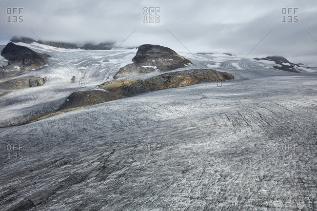 Frozen blackened ice on a glacial mountain in Greenland