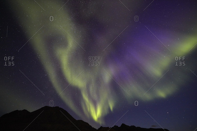 Aurora borealis in the night sky over mountains in Greenland