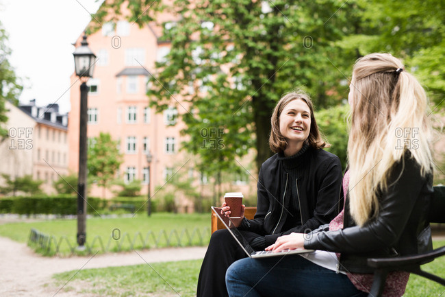 College girls sitting on bench drinking coffee and using laptop
