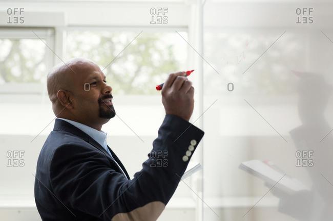 Professor writing on whiteboard in a classroom