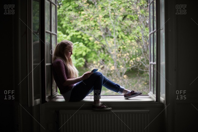 Young woman sitting in windowsill using a tablet