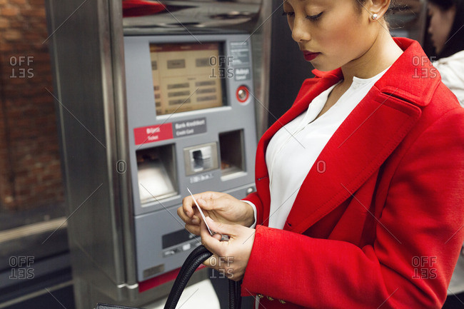 Young woman purchasing train ticket at a kiosk