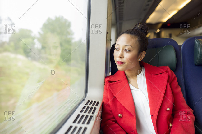 Young woman sitting on a train looking out window